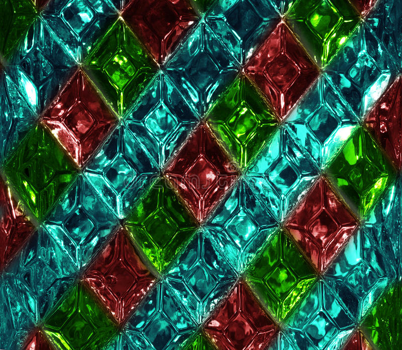 Red, green, turquoise glass texture with a pattern of rhombuses. Clear glass diamond shape. Crystals stock images