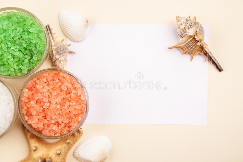 Red, green and white sea salt in glass containers with seashells and starfish with blank white paper card for text royalty free stock photo