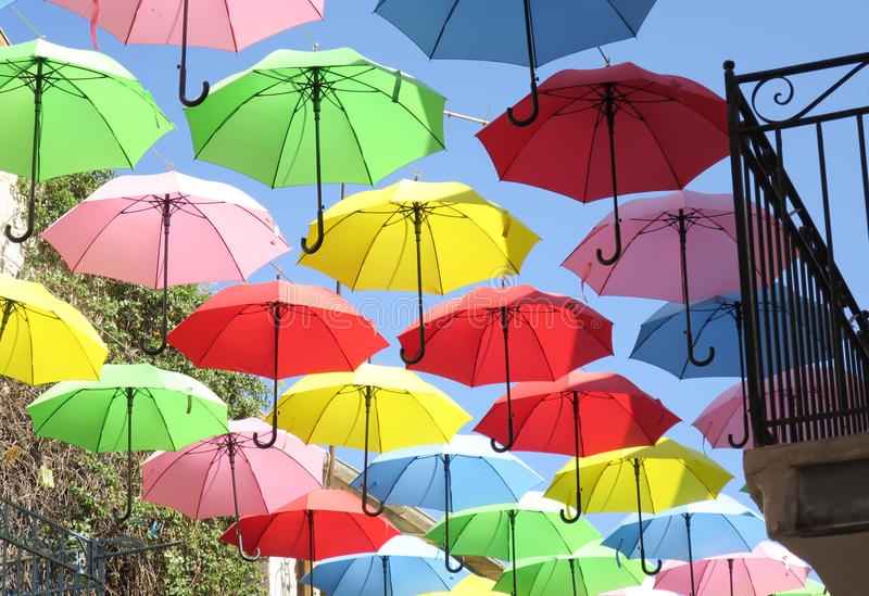 Red, green, yellow, pink, umbrellas flying over city street stock images