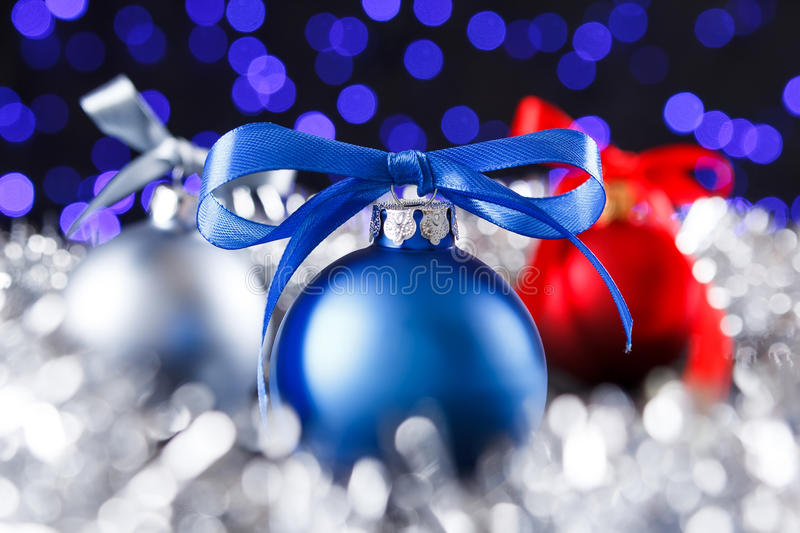 Red, grey and blue christmas balls, blured purple lights at the background. Red christmas ball and blured purple blue and white lights at the background stock images