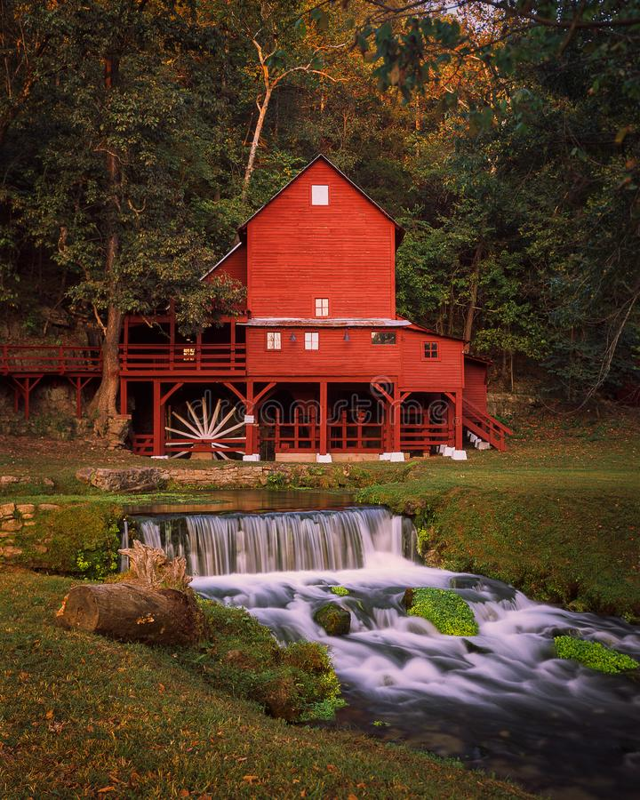 Red Grist Mill in the Summer. Red Water Mill with a stream and waterfall flowing infront royalty free stock photography