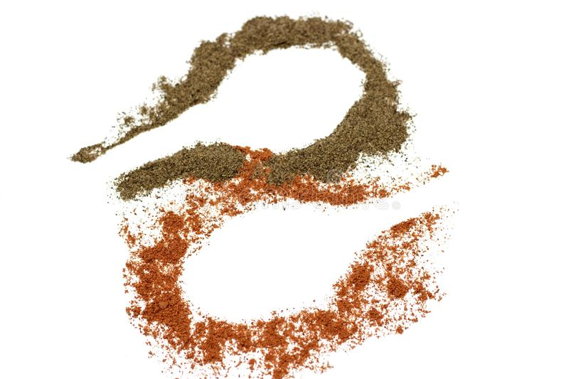 Red ground paprika and black pepper isolated on white background, trail from a spoon stock images