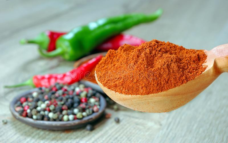 Red ground pepper in a wooden spoon. close up. royalty free stock photography