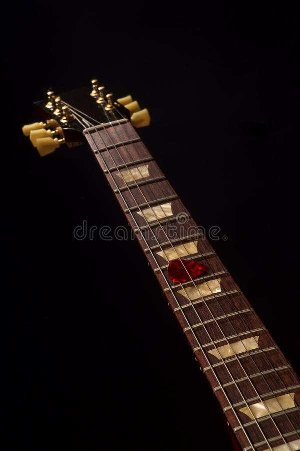 Red guitar pick on the fingerboard and dark royalty free stock photo