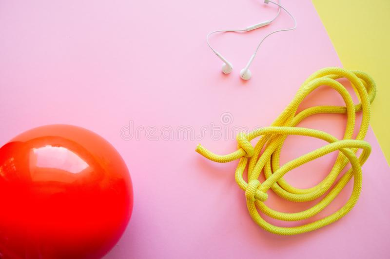Red gymnastic ball, headphones and skipping rope on a pink and y. Ellow background. Sport, hobby and lifestyle concept. Top view and copy space stock photography