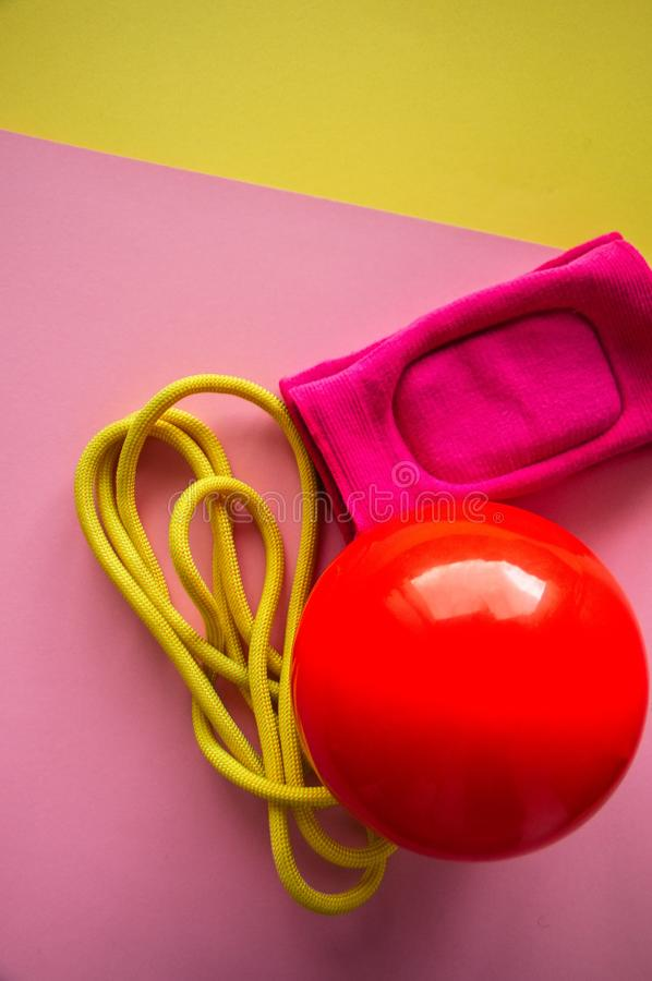 Red gymnastic ball, kneepads and skipping rope on a duotone back. Ground. Sport, hobby and lifestyle concept. Top view and copy space royalty free stock photography