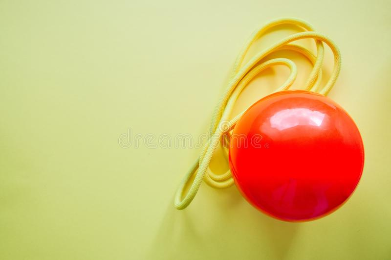 Red gymnastic ball and skipping rope on a yellow background. Sport, hobby and lifestyle concept. Top view and copy space. stock images