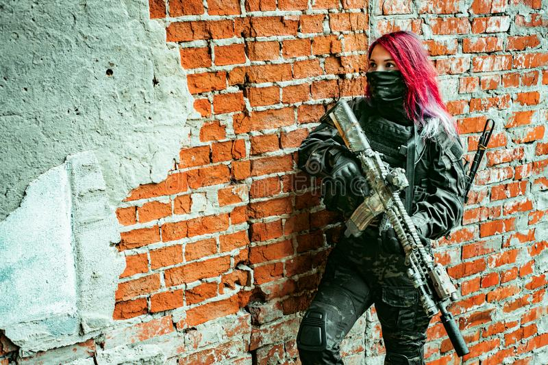 Red-hair airsoft woman in uniform with machine-gun, stand beside brick wall inside broken building. Horizontal background royalty free stock photo