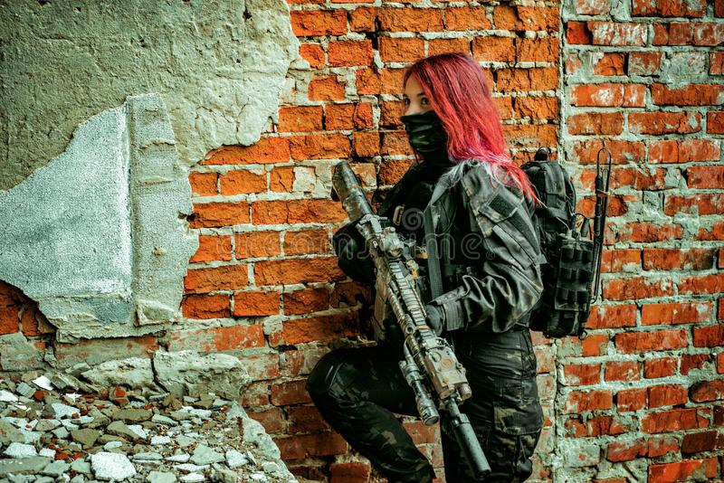 Red-hair airsoft woman in uniform with machine-gun, stand beside brick wall inside broken building royalty free stock image
