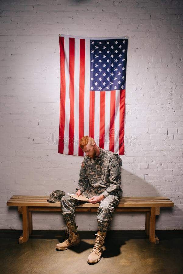Red hair american soldier with letter sitting on wooden bench with flag on white brick wall behind americas independence. Day concept stock photos