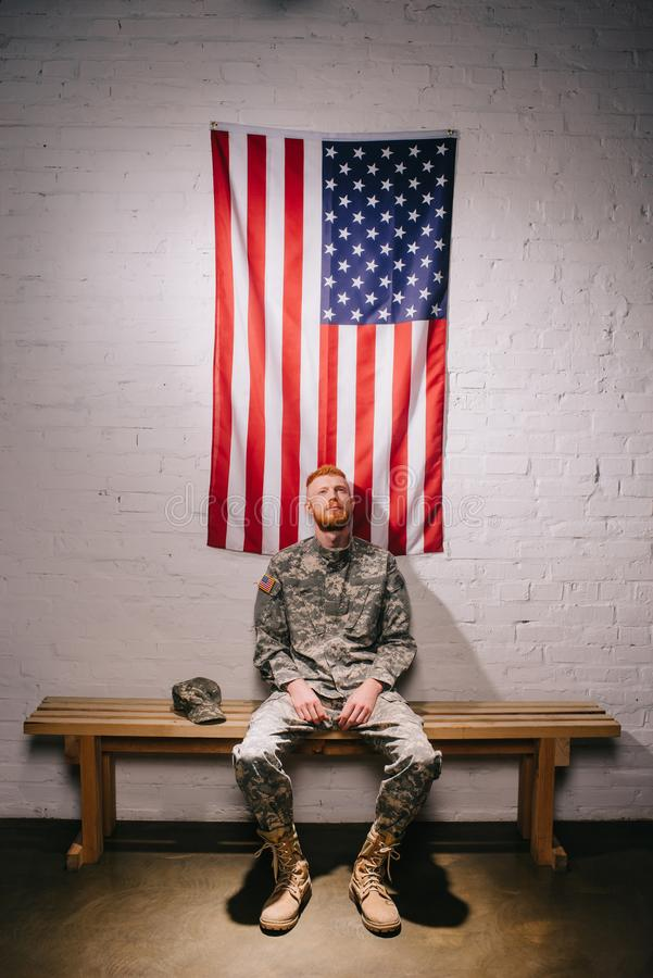 Red hair american soldier sitting on wooden bench with flag on white brick wall behind americas independence. Day concept royalty free stock image