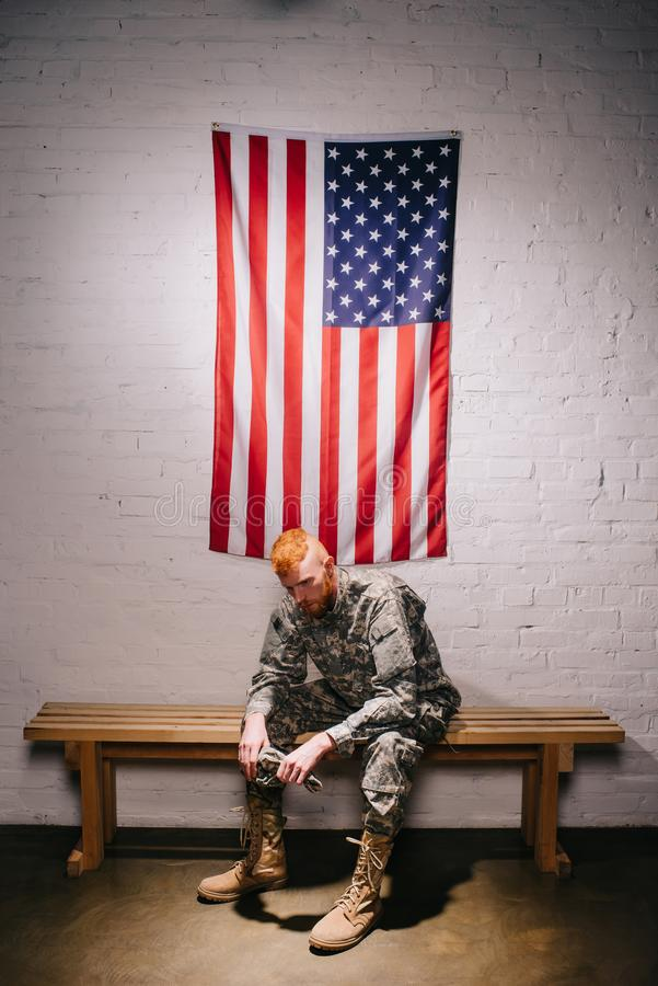 Red hair american soldier sitting on wooden bench with flag on white brick wall behind americas independence. Day concept stock photo