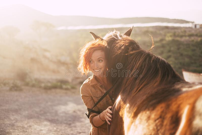 Red hair beautiful alternative lady hug her best friends animal horse during the sunset in the country side. backlight in stock image