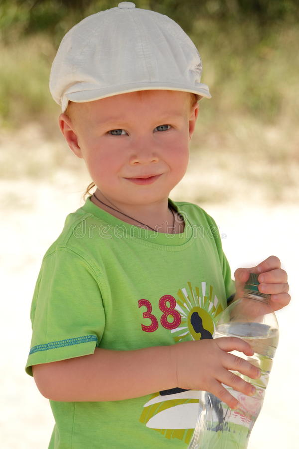 Red hair boy open air with water bottle. In white cap stock image