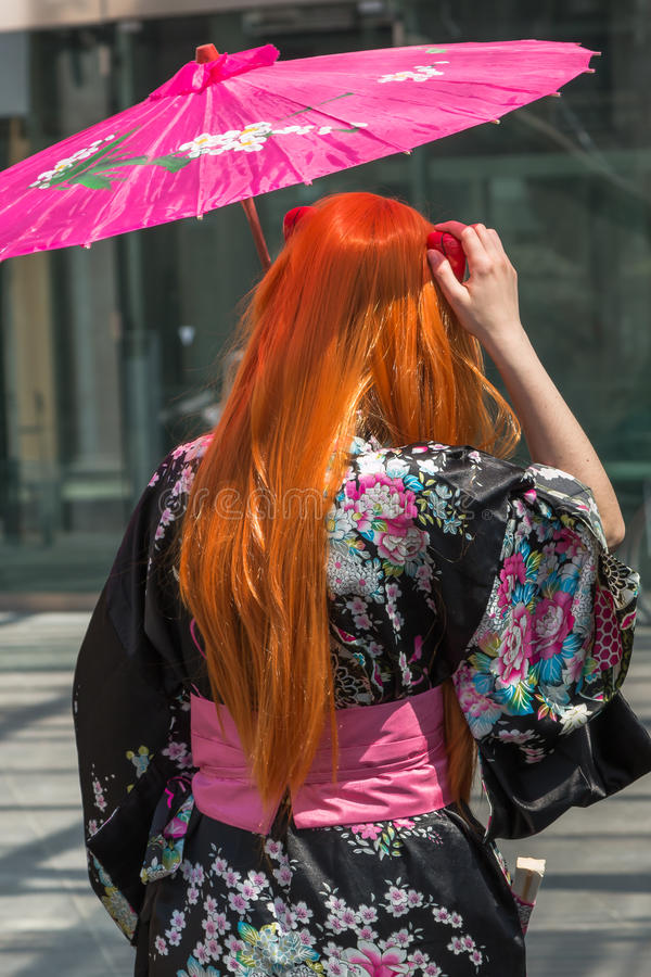 Red Hair Girl with Traditional Japanese Pink Wagasa Umbrella stock image