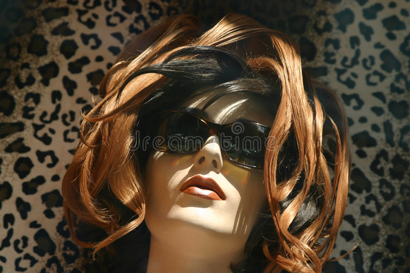 Red hair mannequin. On a leopard background stock photos