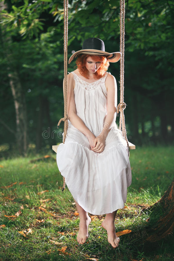 Red hair woman is thinking on a swing. Red hair woman on a swing in the forest is deeply thinking stock photography