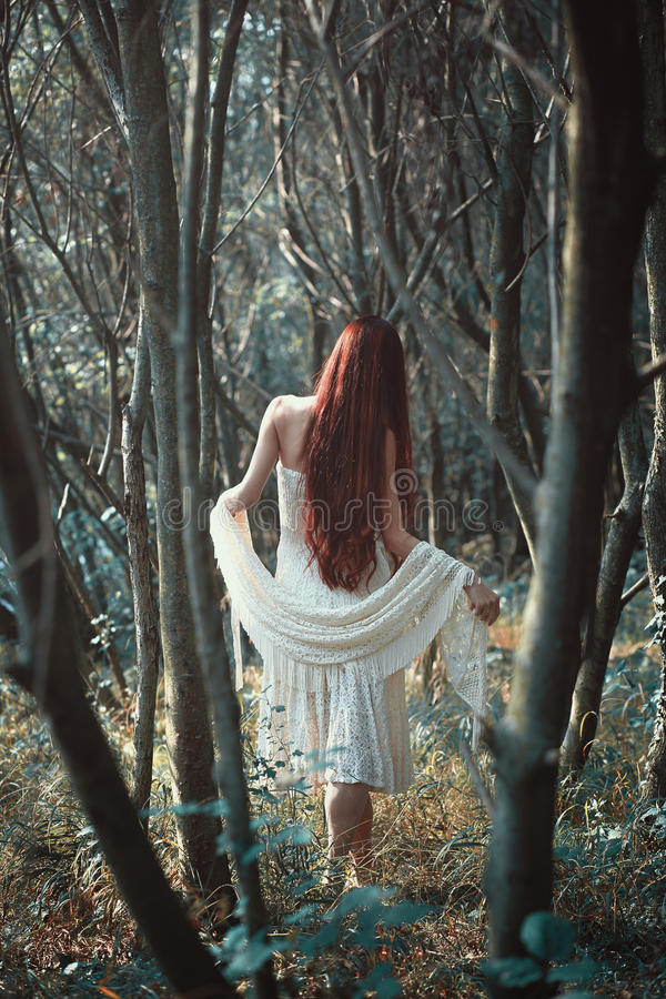Red hair woman in weird forest stock photography