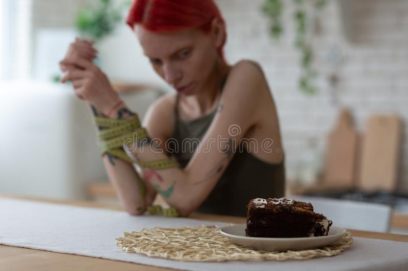 Red-haired anorexic woman looking at plate with dessert stock image