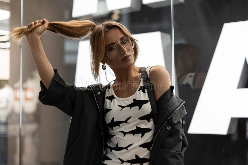 Red-haired attractive hipster young woman in fashionable clothes in stylish glasses standing and holding hair in her hand. Near the modern glass wall in the royalty free stock images