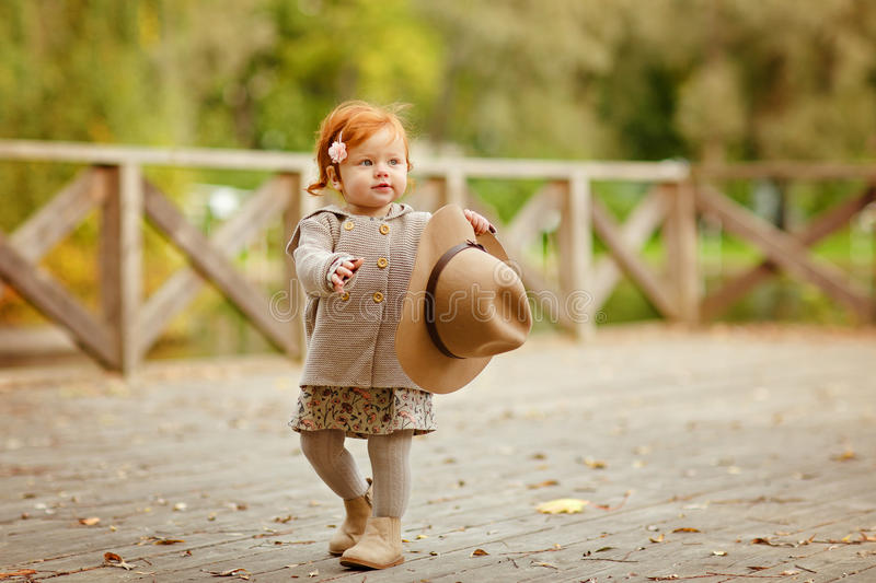 Red-haired baby girl in a hat smiling outdoors in autumn stock photos