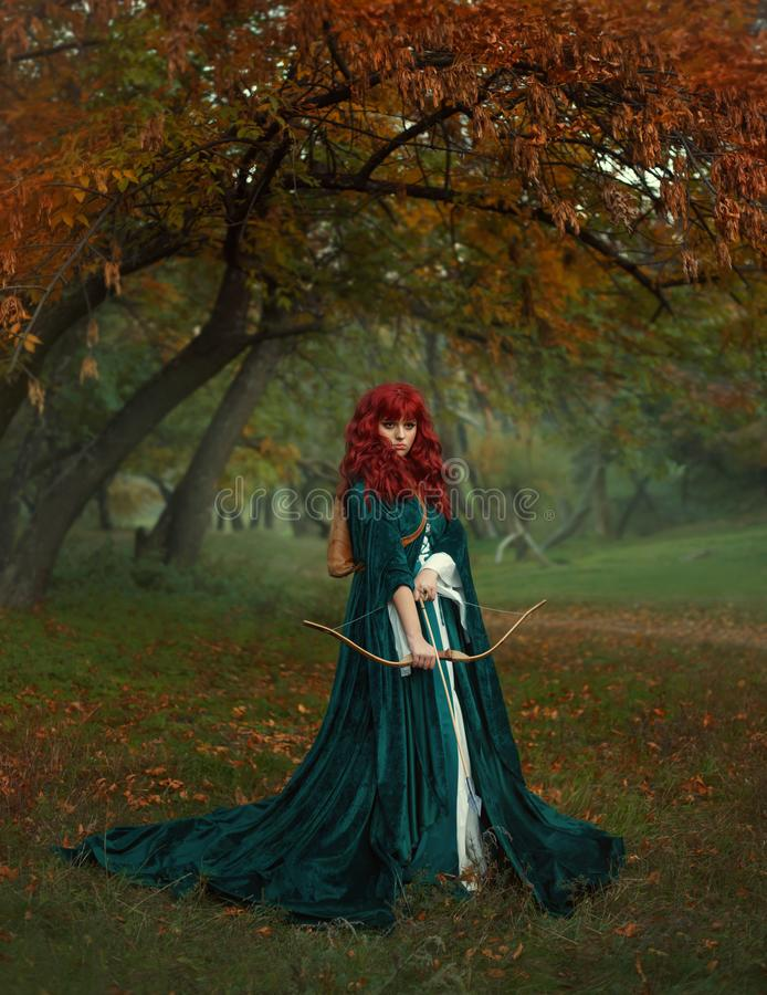 Red-haired beauty in search of the victim, the legend of Robin Hood, mysterious lady in green velvet long raincoat with stock photos