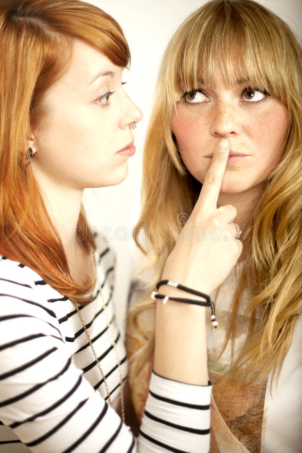 Red haired and blond girl sign to shut up. With finger stock image