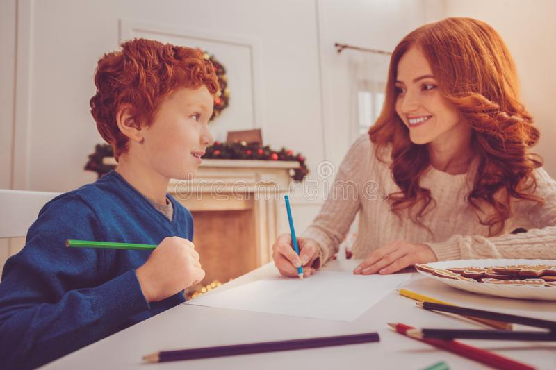 Red-haired boy and his mother drawing gingerbread man together stock photo