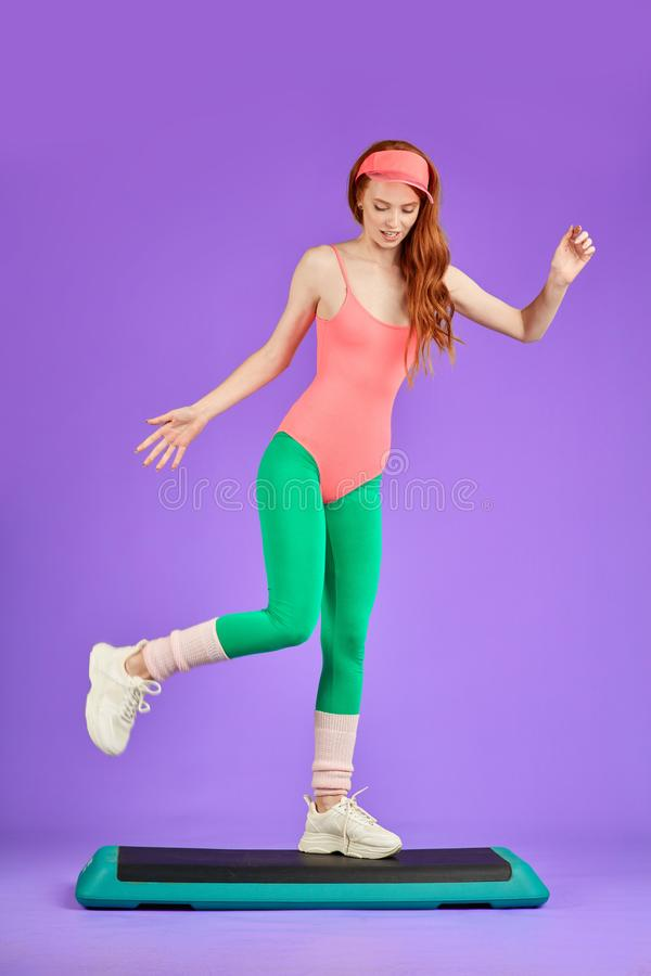 Fitness girl having fun after dynamic workout, dancing on the step. Red haired fitness girl having fun after dynamic workout, dancing on step, moving actively royalty free stock image