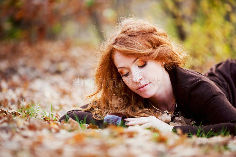 The red-haired girl in autumn leaves stock photos