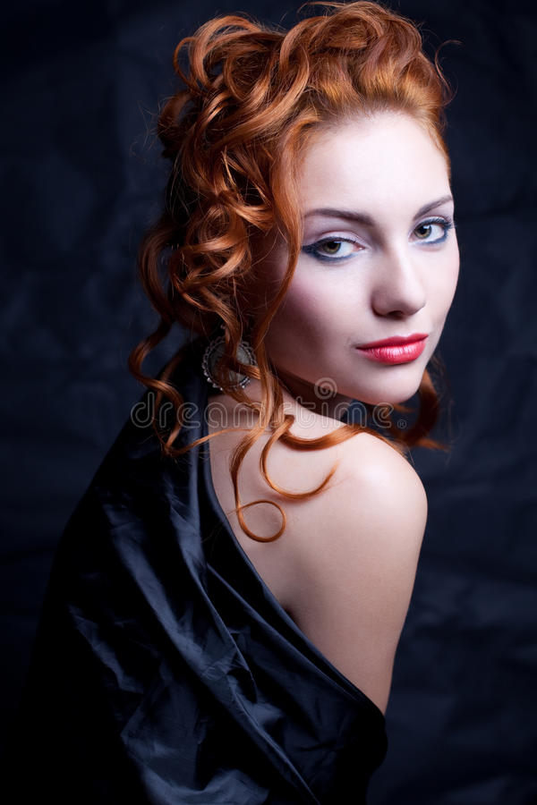 Red-haired girl in black. Vintage portrait of a glamourous queen like girl over wrinkled black paper background. Retro style. Studio shot royalty free stock images