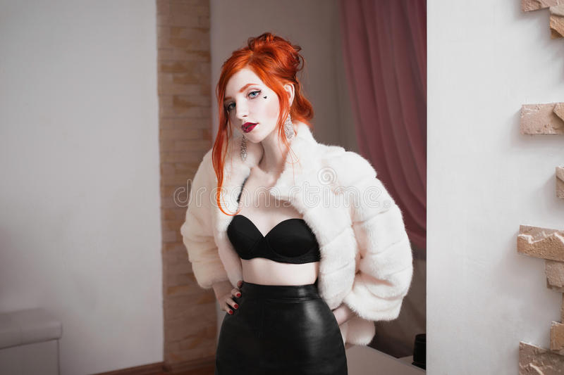 Red-haired girl with blue eyes and red lips in luxurious white fur coat royalty free stock image