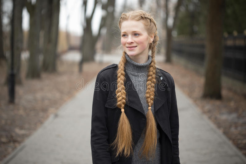 Red-haired girl with braids spring in nature. royalty free stock photography