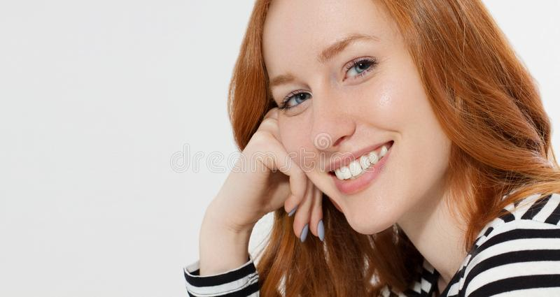 Red haired girl with close up macro face and perfect white teeth smile  on white background. Woman beauty and skin care. No make up concept. Redhead beautiful royalty free stock photos