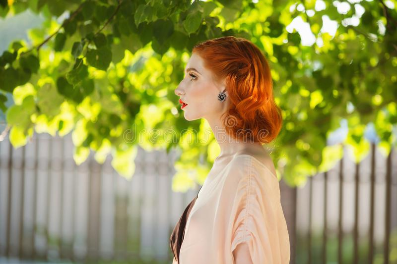 Red-haired girl in a free flying dress and retro hairstyle against a summer background. royalty free stock photo