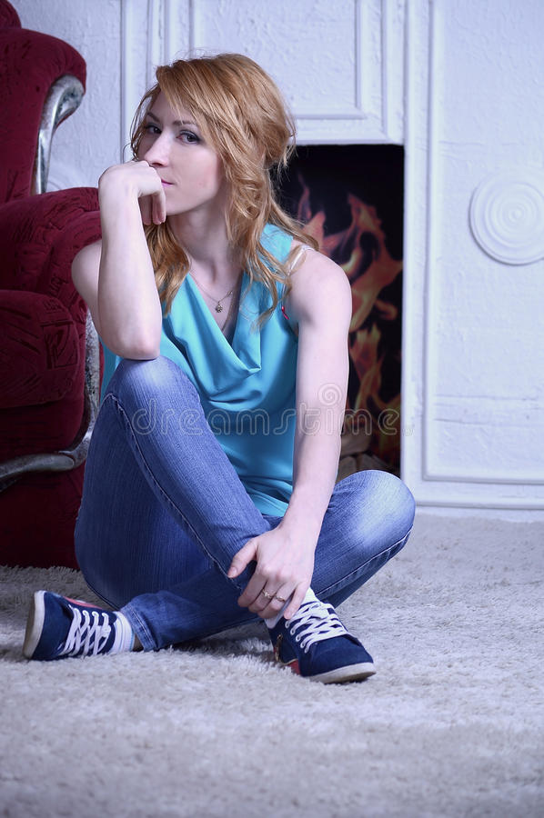 A red-haired girl in front of the fireplace royalty free stock photography