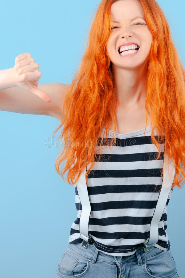 Red-haired girl frowns, grins and shows thumb down royalty free stock photo