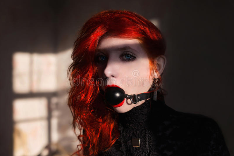 Red-haired girl with a gag. In her mouth royalty free stock image