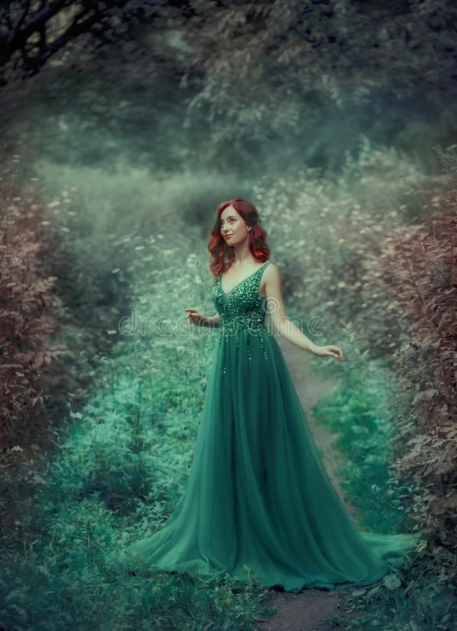 Red-haired girl in a green, emerald, luxurious dress in the floor, with a long train. The princess walks in a fairy. Forest. Simple and elegant hair in large stock images