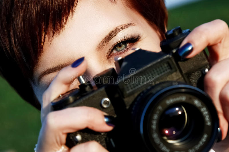 Red-haired girl with green eyes taking pictures camera in the ci royalty free stock image