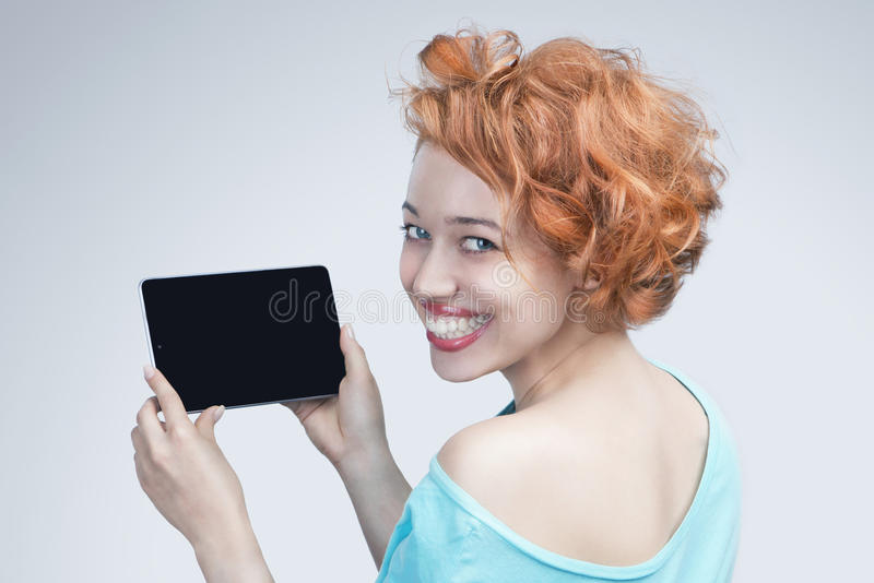 Red-haired girl holding a tablet computer. Woman is smiling wide and beautiful smile, looking into the camera. Empty space on the tablet pc, where you can place stock image