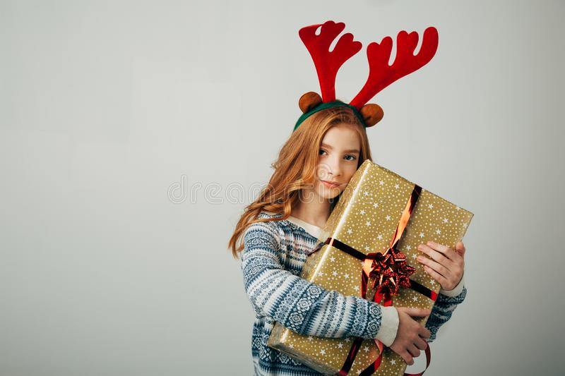Red-haired girl hugs her present from parents at Christmas. The blue-eyed lady is happy about the New Year`s gift from royalty free stock image