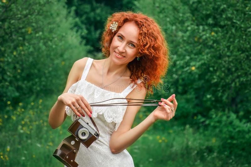 The red-haired girl in a lace dress laughs and looks at the camera. Holding a retro camera in hands. Around it is a summer green royalty free stock photo