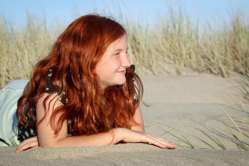 Red haired girl lying on a white sandy New Zealand beach stock photo