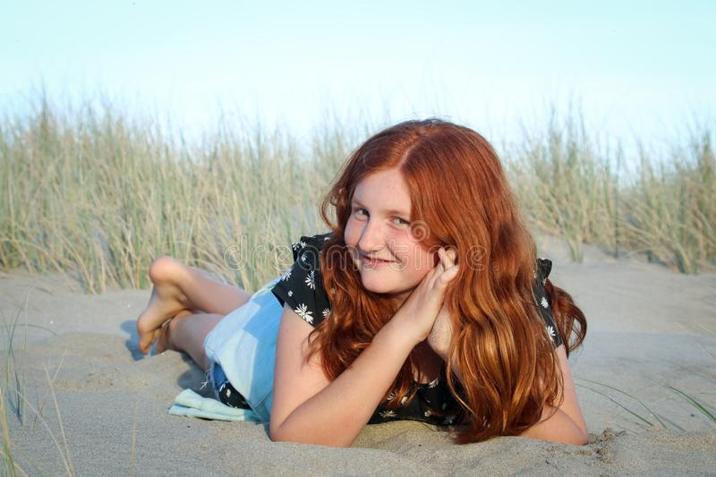 Red haired girl lying on a white sandy New Zealand beach stock photography