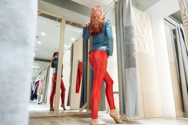 Red-haired girl measures red leather pants. beautiful woman reflected in the mirror. lady buys clothes. bottom view royalty free stock photos