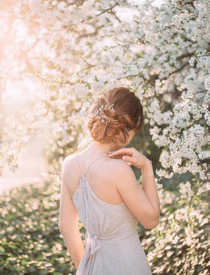 Red-haired girl in a modest, gray dress in rustic style. Portrait of the bride against the background of a flowering stock photography