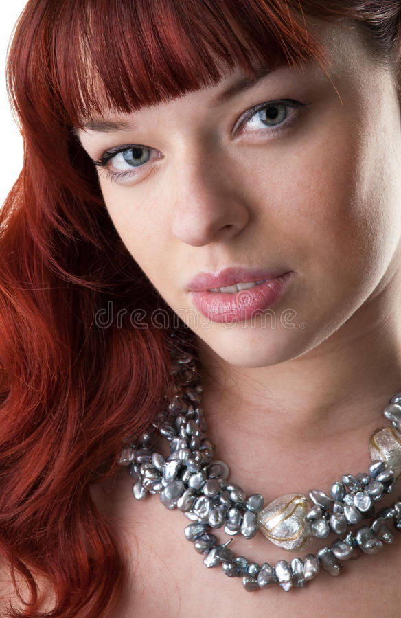 Red haired girl and a pearl necklace stock photo