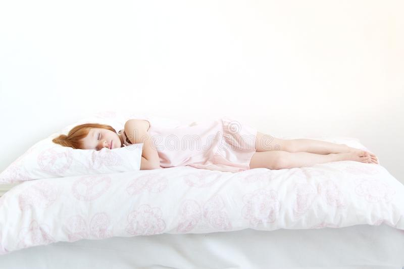 Red-haired girl in a pink dress. Is sleeping on the bed stock image