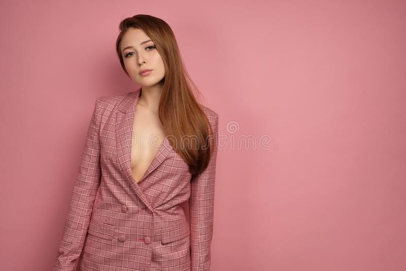 Red-haired girl in a pink jacket stands on a pink background and looks at the camera with her head bowed to the side. royalty free stock photography